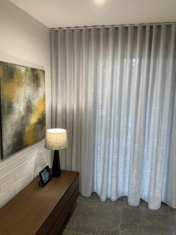 Light grey Sheer wavefold curtains in living room with abstract art