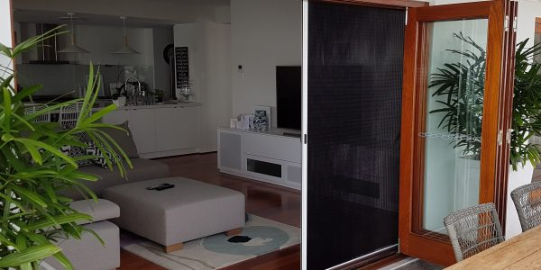 Pleated screens on bi-folding doors showing partially open